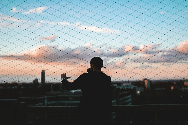 Man standing behind chain link fence looking out over a cityscape